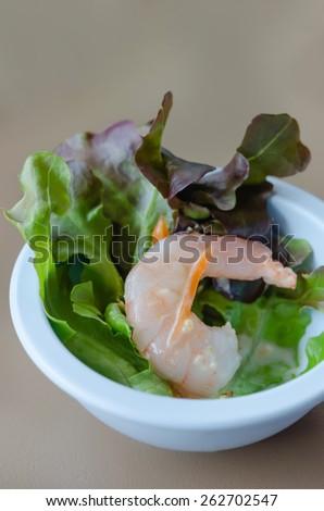 Oak leaf lettuce salad with shrimps in blue bowl - stock photo
