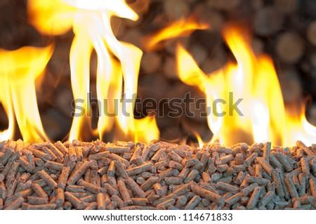 Oak Pellets in  flames- chopped firewood background - stock photo