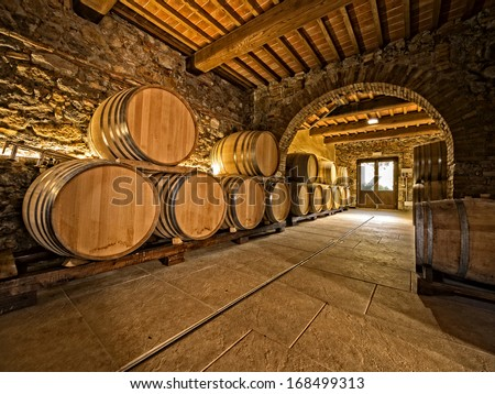 oak wine barrels in winery cellar with vaulted arches - stock photo