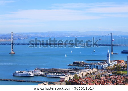 Oakland Bay Bridge in San Francisco and port tower - stock photo