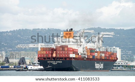 Oakland, CA - April 24, 2016: Tugboat AHBRA FRANCO at the stern of Cargo Ship ROTTERDAM EXPRESS, assisting the vessel to maneuver into the Port of Oakland.  - stock photo