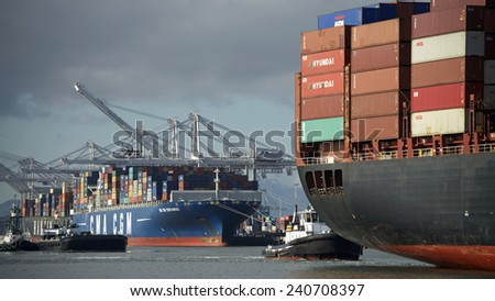 OAKLAND, CA - DECEMBER 29, 2014:  Cargo Ship APL HOLLAND entering the Inner Harbor at the Port of Oakland with Tugboat DELTA CATHRYN following at the Stern. POINT VINCENTE following, towing a barge. - stock photo