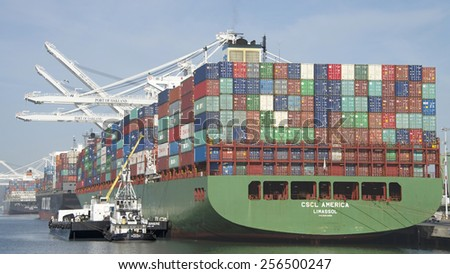 OAKLAND, CA - FEBRUARY 26, 2015: ROYAL MELBOURNE Tugboat with BERNE BRIER Barge providing Maritime Services for CSCL Cargo Ship AMERICA while loading at the Port of Oakland. - stock photo