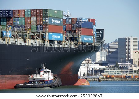 OAKLAND, CA - FEBRUARY 24, 2015: Tugboat PATRIOT performing assistive maneuvers with Hanjin Cargo Ship LONG BEACH entering the Port of Oakland. A tugboat maneuvers vessels by pushing or towing them. - stock photo