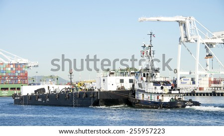 OAKLAND, CA - FEBRUARY 24, 2015: Tugboat ROYAL MELBOURNE pushing BERNIE BRIERE, a double hulled barge, past the Port of Oakland. Tugs move vessels that should not or can not move themselves. - stock photo