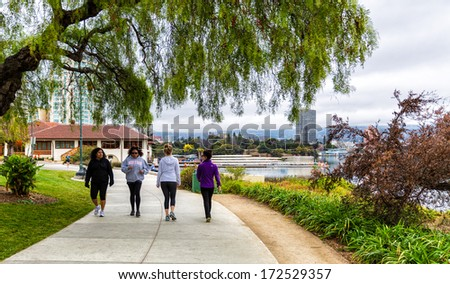 OAKLAND,CA-JAN.11,2014:People on the newly paved 3.4 mile pedestrian path around Lake Merritt in downtown Oakland.The lake was recently renovated, adding new parks and an amphitheater. - stock photo