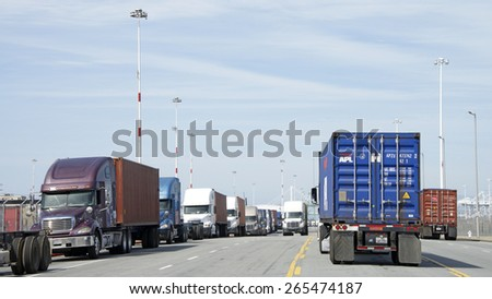 OAKLAND, CA - MARCH 30, 2015: Hundreds of trucks line Middle Harbor Road waiting to enter the docks at the Port of Oakland.  - stock photo
