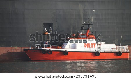 OAKLAND, CA - NOVEMBER 27, 2014: Pilot Vessel GOLDEN GATE approaches APL Cargo Ship PARIS at the ships Port side opening to pick up a package mid departure from the Port of Oakland. - stock photo