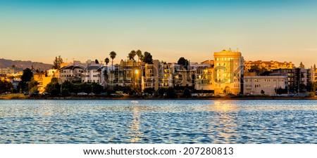 Oakland, California Lake Merritt waterfront buildings at sunset - stock photo