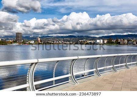 Oakland California view across Lake Merritt of the north shore and the Oakland Piedmont hills, on a day with dramatic storm clouds reflected in the water. Viewed from the new south shore bridge area. - stock photo