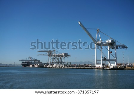 OAKLAND - OCTOBER 12: Shipping Cargo Boats line up in harbor under giants unloading cranes in Oakland Harbor and San Francisco in the distance.  Oakland California on October 12, 2015. - stock photo