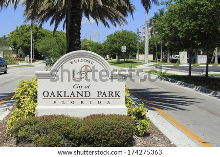 OAKLAND PARK, FLORIDA - MAY 7, 2013: Cement sign with buildings and tree graphic welcoming people to the city of Oakland Park, Florida on a tropical foliage street median on a sunny blue sky day. - stock photo