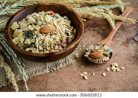 Oat and whole wheat grains flake in wooden bowl on wooden table - stock photo