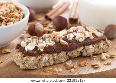oat bar with chocolate on wooden board, selective focus, close-up - stock photo
