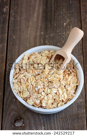 Oat, barley and wheat flakes in a ceramic bowl  - stock photo