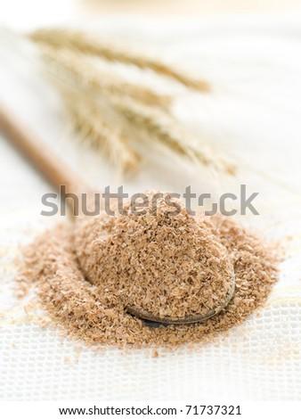 Oat bran in wooden spoon on kitchen towel - stock photo
