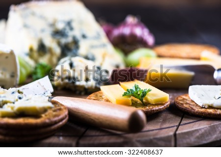 Oat crackers with cheese selection on wooden rustic board - stock photo