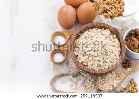 oat flakes and ingredients on a white wooden table, horizontal, top view, close-up - stock photo