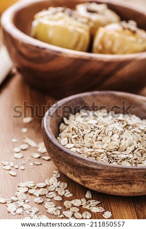 Oat flakes in bowl on wooden table. - stock photo