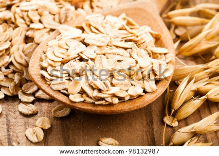 Oat flakes in spoon on wooden table - stock photo