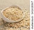 Oat flakes in white ceramic bowl on sackcloth background - stock photo