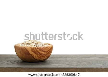 oat flakes in wood bowl on oak table, white background - stock photo