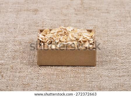Oat flakes on linen - stock photo