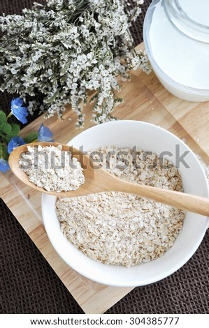 oat flakes on wooden spoon put on oat bowl - stock photo