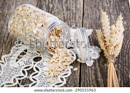 Oat flakes spilled out from glass jar. - stock photo