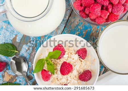 Oat flakes with milk and raspberries for breakfast Jug and glass with milk, spoon, napkin, fresh mint on an old wooden blue background, top view. The concept of a healthy diet, weight loss  - stock photo