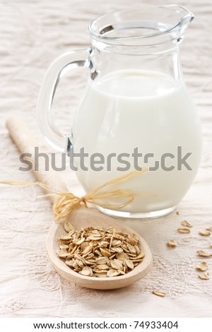 Oat flaks on a wooden spoon and jug of milk. - stock photo