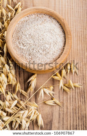 Oat meal in bowl on the wooden table - stock photo