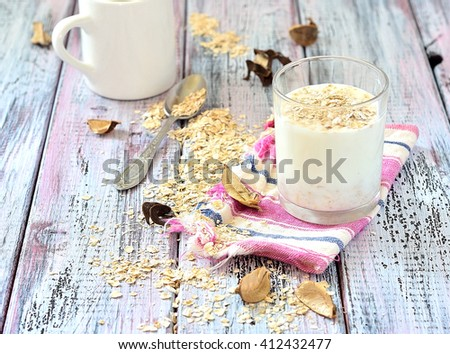 Oat milk in a glass on the table with dried fruit - stock photo