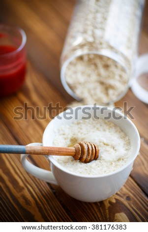 Oat milk porridge and honey in a cup on the table - stock photo
