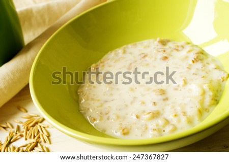 Oat milk porridge in a green bowl on the table with oats - stock photo