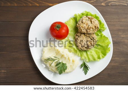 Oat Patty with vegetables, tomato and mashed potatoes. Laid out on a white plate, decorated with greenery - stock photo
