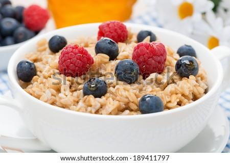 oat porridge with fresh berries, close-up, horizontal - stock photo