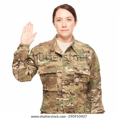 Oath of enlistment. Attractive female Army soldier wearing multicam camouflage. - stock photo
