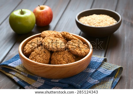 Oatmeal and apple cookies in wooden bowl with apples and oatmeal in the back, photographed with natural light (Selective Focus, Focus on the front of the cookie in the middle) - stock photo