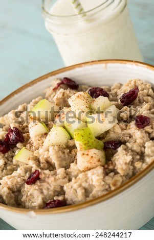 Oatmeal breakfast cereal with glass of milk and apples and cranberries - stock photo