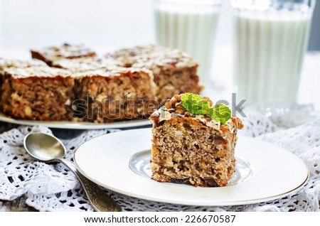 oatmeal cake with dates and walnuts on a light background. tinting. selective focus on mint - stock photo