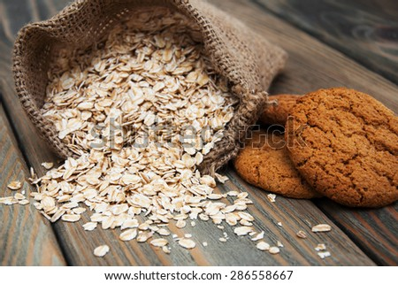 Oatmeal cookies with oat flakes on a old wooden background - stock photo