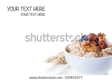 Oatmeal porridge in bowl topped with fresh blueberries, nuts and honey on white background - stock photo