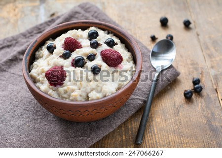 Oatmeal porridge in brown ceramic bowl with berries: raspberries and blackberries - stock photo