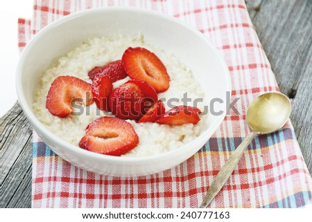Oatmeal porridge topped with fresh strawberries in white bowl on red plaid napkin, close up - stock photo
