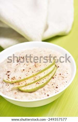 Oatmeal porridge with apples and cinnamon in white bowl - stock photo