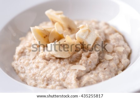 oatmeal porridge with banana  slices and almonds close-up on white plate  - stock photo