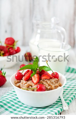 Oatmeal porridge with berries in a white bowl - stock photo
