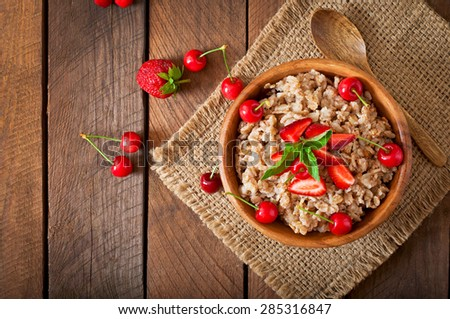 Oatmeal porridge with berries in a wooden bowl. Top view - stock photo