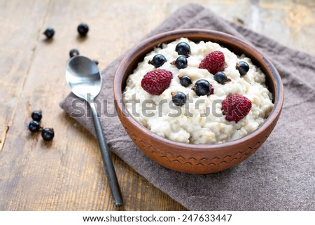 Oatmeal porridge with blackberries and raspberries in brown ceramic bowl on wooden table - stock photo